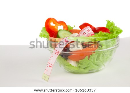 Picture of a plate with greek salad and tape- measure on table