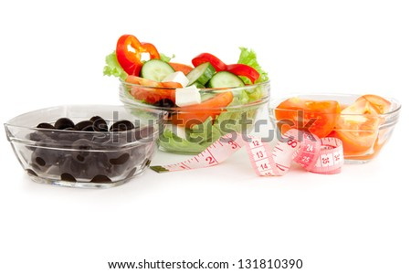 Picture of a plates with greek salad, tomatoes  and black olives on table