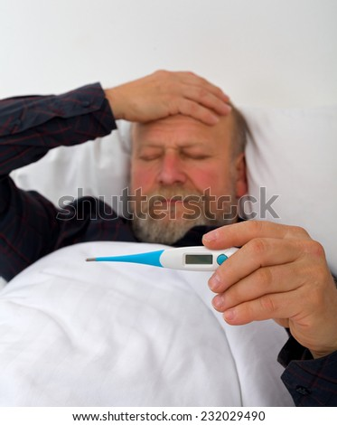 Picture of a sleeping elderly man with headache - stock photo