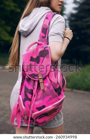 Picture of a slim girl, carrying on her back a bright pink backpack - stock photo
