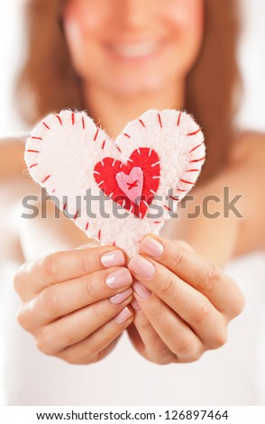 Picture of a small white heart in hands, female holds handmade sewn soft toy, macro, shallow dof, woman with Valentine gift, happy girl smiling, conceptual image of health care or love - stock photo