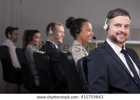 Picture of a smiling call centre consultant and his workmates