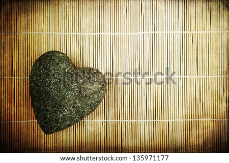 picture of a stone heart on a bamboo mat overlaid with an attractive vintage style texture