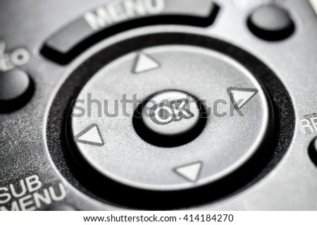 Picture of a television remote control directional dial and buttons close-up