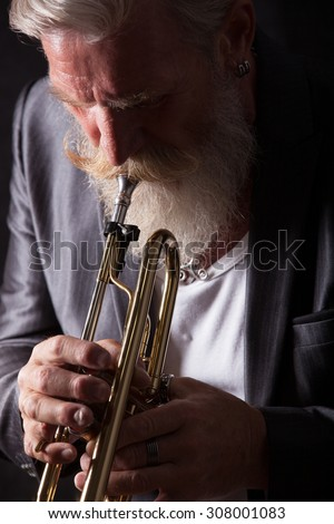 PIcture of a white haired trumpet player with a long white beard. Profile picture with side light.