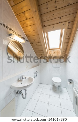 picture of a white tiled restroom with tiolet, basin, mirror and light. - stock photo