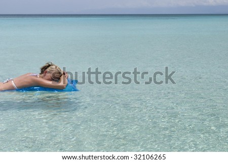 Picture of a woman floating on the smooth, crystal clear Caribbean waters. Shot at Bahia de las Aguilas beach in the Dominican Republic. - stock photo