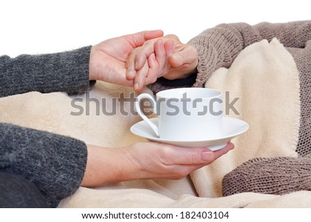 picture of a woman hand giving tea to an elderly woman - stock photo