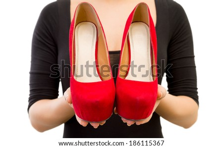 Picture of a woman hand holding red high heels