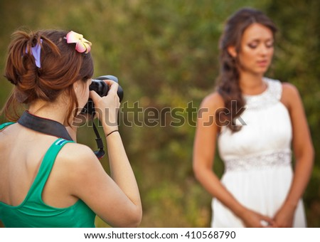 Picture of a woman photographer making a photo of a bride - stock photo