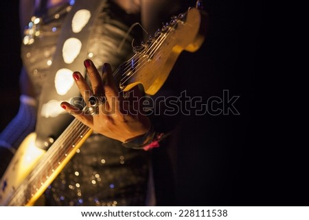 Picture of a woman playing electric guitar - stock photo