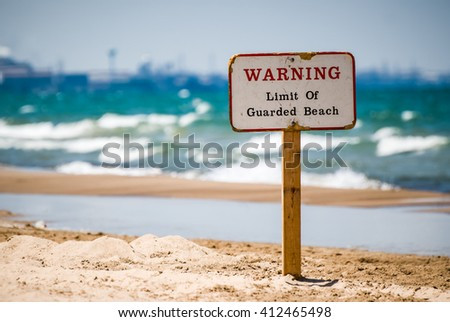 Picture of a wooden warning sign in the sand at the beach indicating the limit of lifeguard patrol coverage. - stock photo