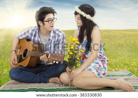Picture of a young Asian man playing guitar for his girlfriend on the meadow, shot in the springtime - stock photo
