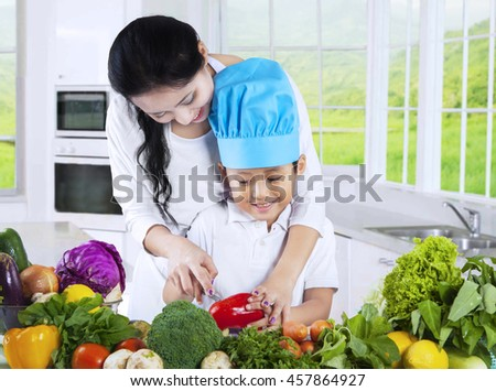 Picture of a young Asian mother cooking vegetables with her son in the kitchen at home