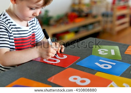 Picture of a young boy learning to write numbers on colorful cards with a focus on his hand and his pen - stock photo