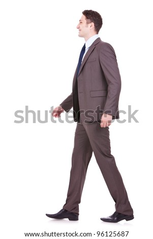 picture of a young business man walking forward on white background. side view of a young businessman walking