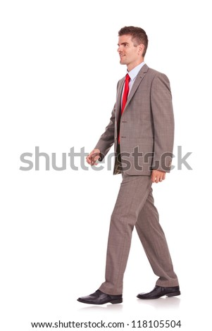 picture of a young business man walking forward - side view - stock photo