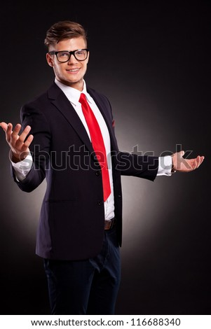 picture of a young business man welcoming you with a smile on his face. dark background - stock photo