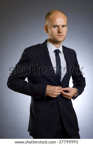 picture of a young businessman buttoning his coat