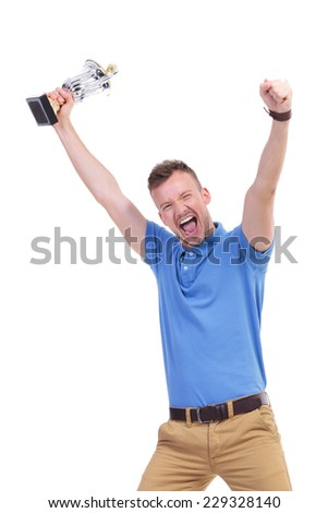 picture of a young casual man holding a trophy and cheering while looking into the camera. isolated on a white background - stock photo