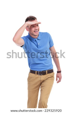 picture of a young casual man looking away and smiling while keeping his hand over his eyes to protect himself from the sun rays. isolated on a white background - stock photo