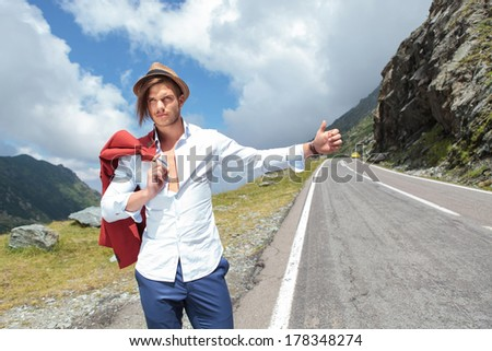 picture of a young fashion man hitchhiking in the mountains with his jacket over his shoulder - stock photo