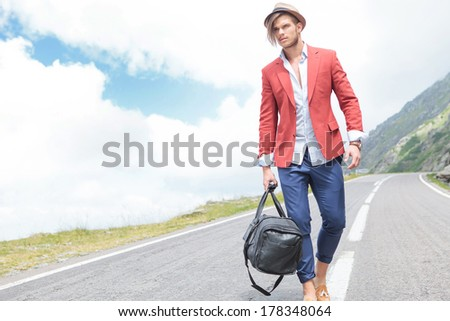 picture of a young fashion man strolling outdoor with a bag in his hand while looking away from the camera - stock photo
