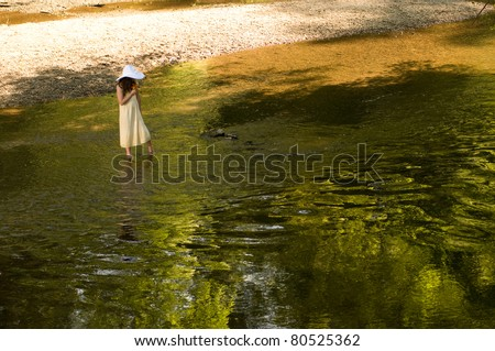 picture of a young girl wading in a  stream