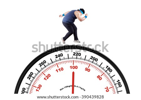 Picture of a young overweight person wearing sportswear and running above a big scale, isolated on white background