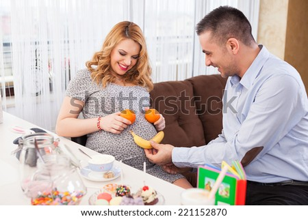Picture of a young pregnant woman and her husband making a smile on her belly with a banana and two oranges, sitting at the kitchen table full of sweets