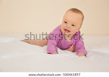 Picture of adorable baby in violet bodysuit sitting on bed