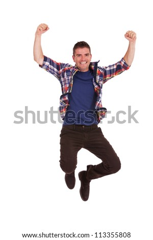 Picture of an ecstatic casual young man, jumping in the air and smiling, with hands raised - stock photo