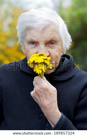 Picture of an elderly woman holding a yellow flower - stock photo