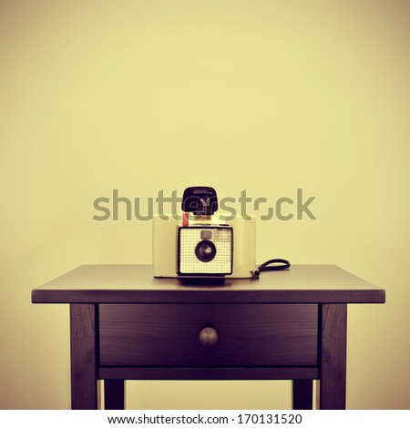 picture of an old instant camera on a bureau, with a retro effect - stock photo