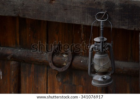 Picture of an old oil lantern hanging from a nail on old battered wood next to a horseshoe.