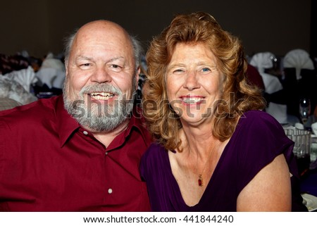 Picture of an older couple celebrating their daughter getting married.  They are at the wedding reception and have great, big smiles.