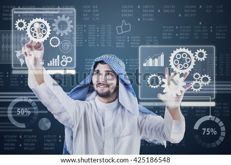 Picture of Arabic entrepreneur working with futuristic screen while wearing traditional clothes - stock photo