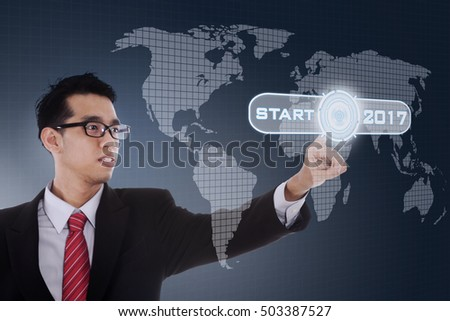 Picture of Asian businessman touching start button with numbers 2017 and world map on the virtual screen