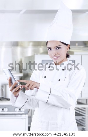 Picture of Asian female chef standing in the kitchen while using mobile phone and wearing uniform