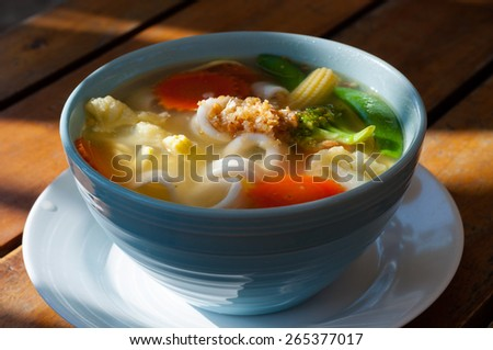 Picture of asian vegetable noodle soup in a white plate