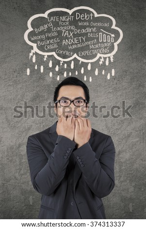Picture of asian worker in business suit biting his nails when facing many problems
