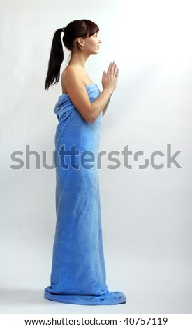 Picture of attractive beautiful woman dressed in blue towel praying. Studio shot. - stock photo