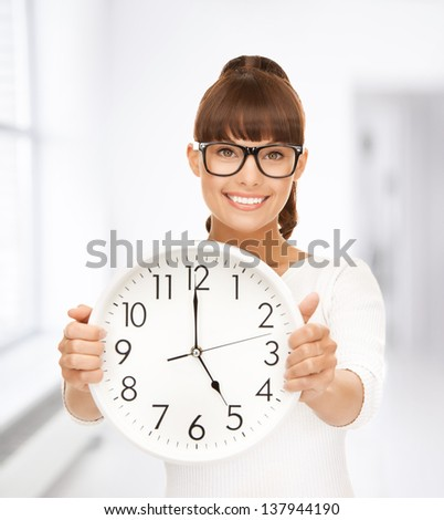 picture of attractive businesswoman with wall clock - stock photo