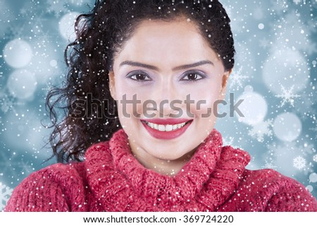 Picture of attractive indian woman smiling at the camera while wearing warm clothes with winter background