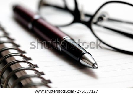 Picture of ballpoint pen and prescription glasses on a spiral notebook