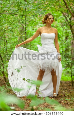 Picture of beautiful bride in white wedding dress at the forest - stock photo