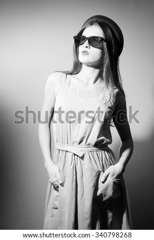 Picture of beautiful exciting young lady in 3d glasses looking up. Black and white photography - stock photo