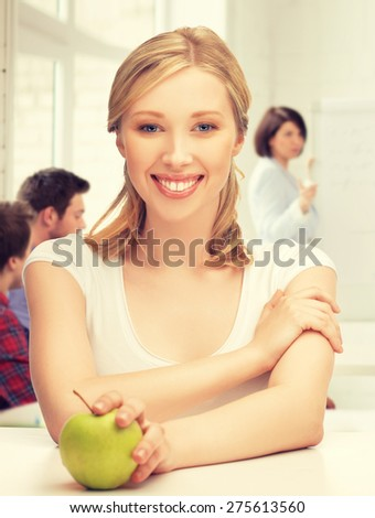 picture of beautiful girl with green apple at school - stock photo