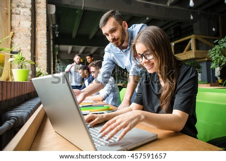 Picture of beautiful lady in glasses listening to her partner or colleague. Businesswoman working on laptop computer in restaurant or cafe.