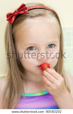 Picture of beautiful little girl eating strawberry in the kitchen - stock photo